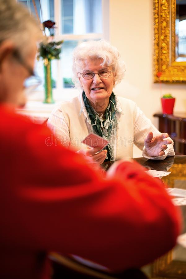 Two elder people playing cards stock images