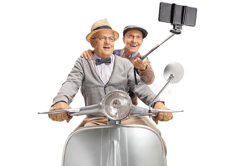 Two elderly gentlemen taking a selfie on a vintage scooter. Isolated on white background stock photo