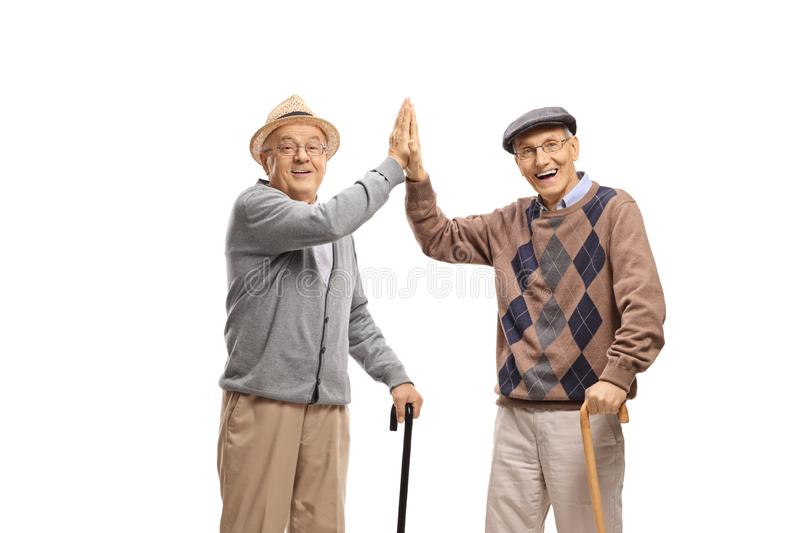Two elderly men with canes gesturing high-five. On white background royalty free stock photo