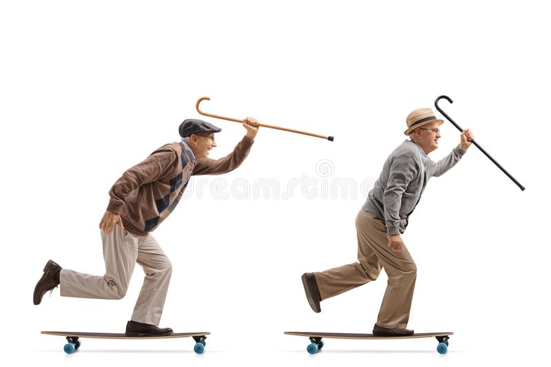 Two elderly men with canes riding longboards. Full length profile shot of two elderly men with canes riding longboards isolated on white background royalty free stock photography