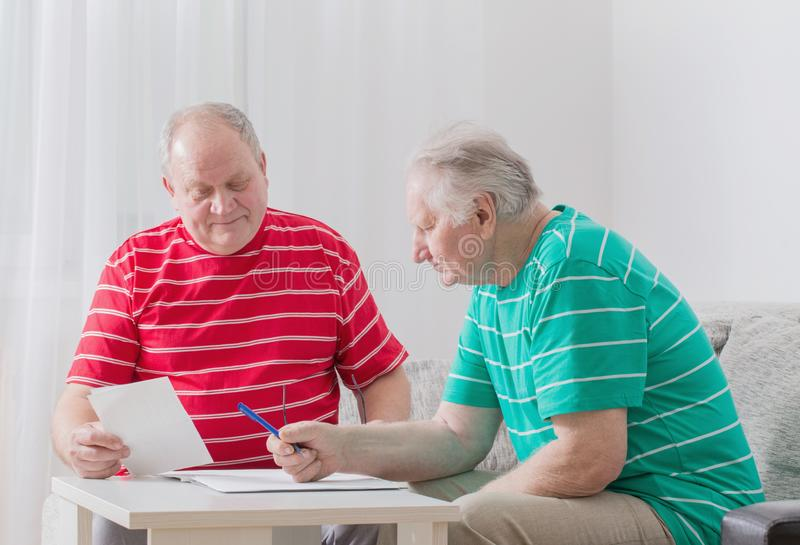 Elderly men with documents. Two elderly men with documents royalty free stock image