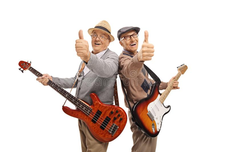 Two elderly men with electric guitars showing thumbs up. Isolated on white background royalty free stock images