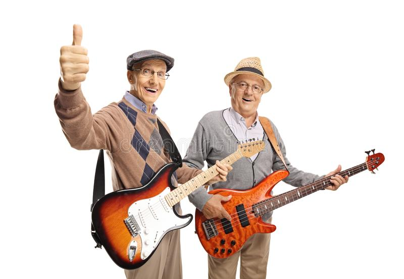 Two elderly men with electric guitars showing thumbs up. Isolated on white background stock image