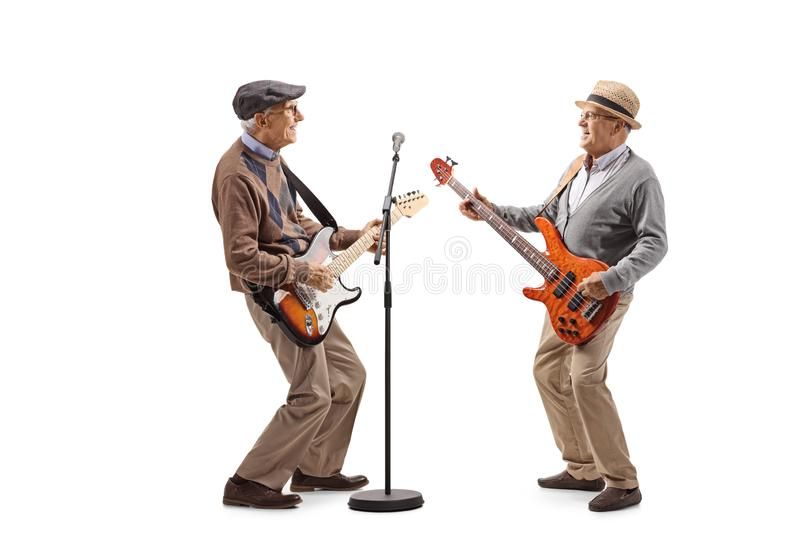 Two elderly men having a jam session with electric guitars royalty free stock image