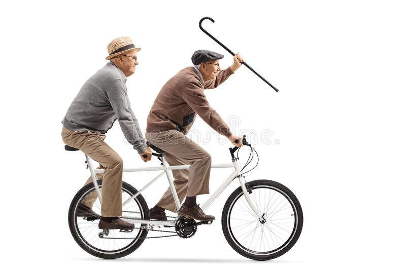 Two elderly men riding a tandem bicycle and waving with a walking cane. Full length shot of two elderly men riding a tandem bicycle and waving with a walking royalty free stock image