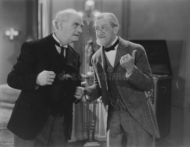 Two elderly men share the gossip royalty free stock images