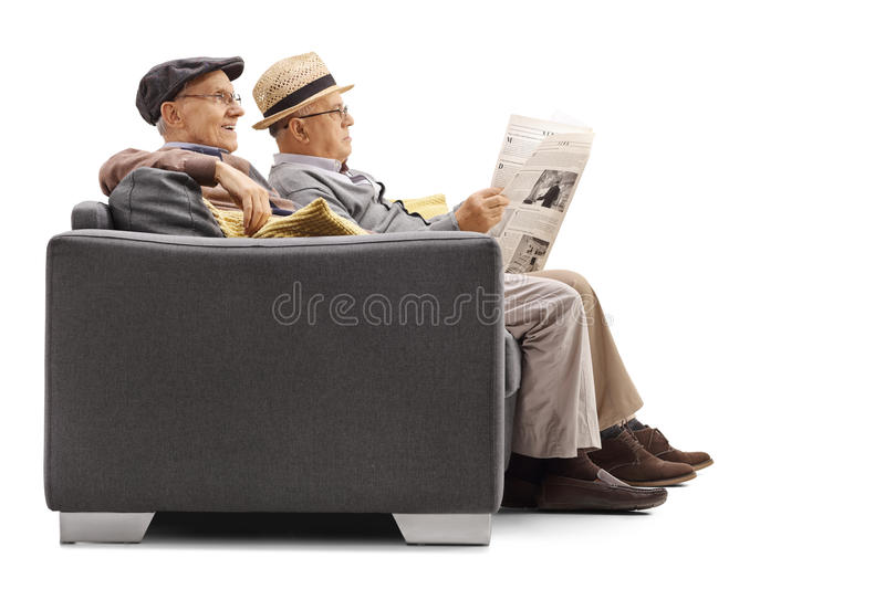 Two elderly men sitting on a sofa with one of them reading a new. Spaper isolated on white background royalty free stock photo