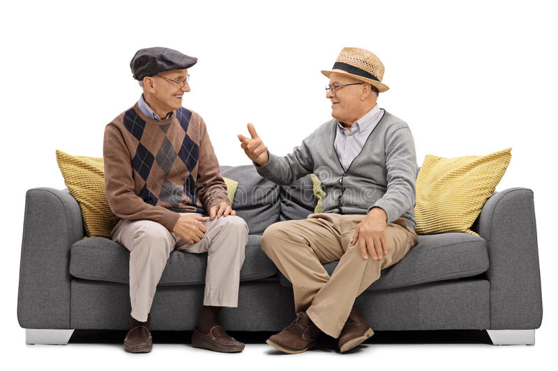 Two elderly men sitting on a sofa and talking. Isolated on white background royalty free stock image