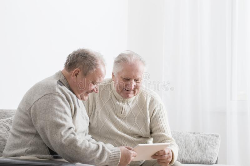 Two elderly men with tablet. Two happy elderly men with tablet stock image