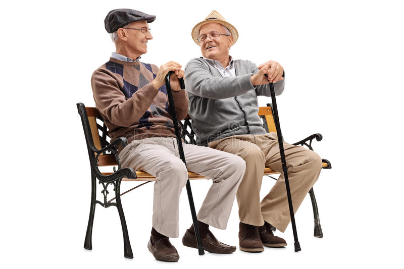 Two elderly men talking to each other. Two elderly men sitting on a wooden bench and talking to each other isolated on white background stock photo