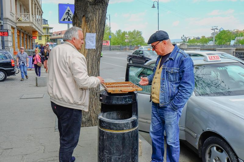 Two elderly men taxi- drivers playing backgammon in the street waiting passengers stock image