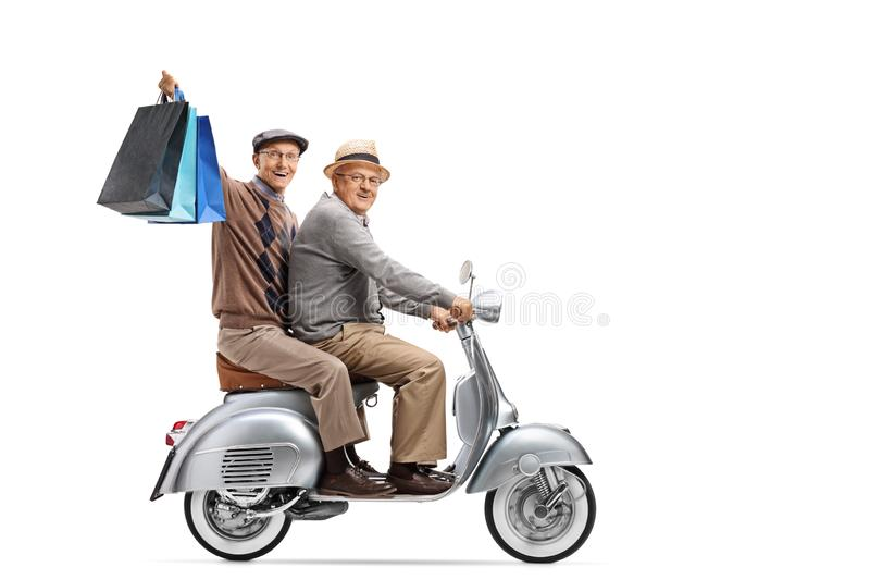 Two elderly men on a vintage scooter with shopping bags. Full length shot of two elderly men on a vintage scooter with shopping bags isolated on white background royalty free stock photography