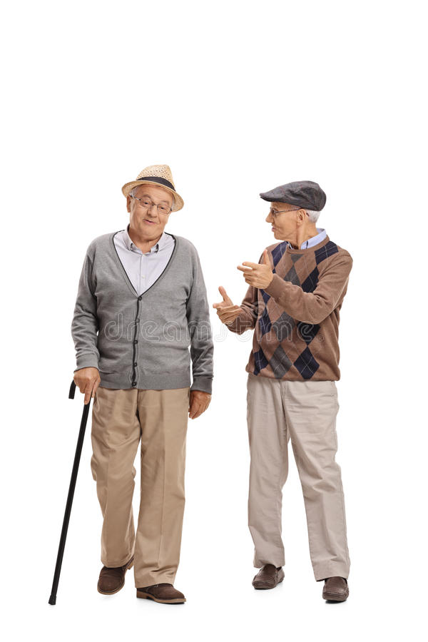 Two elderly men walking towards the camera and talking. Full length portrait of two elderly men walking towards the camera and talking to each other isolated on royalty free stock photo