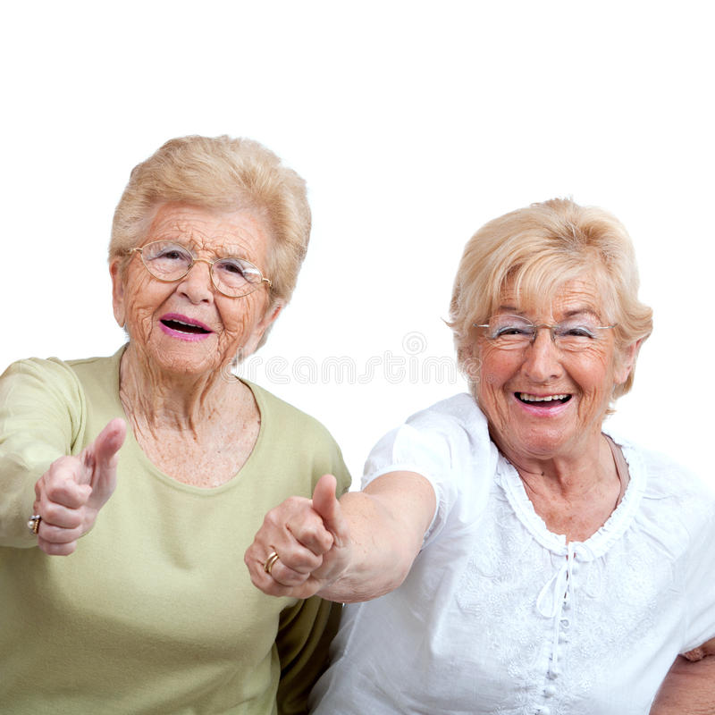 Two Elderly woman showing thumbs up. Close up portrait of two friendly senior women showing thumbs up. Isolated on white royalty free stock photography