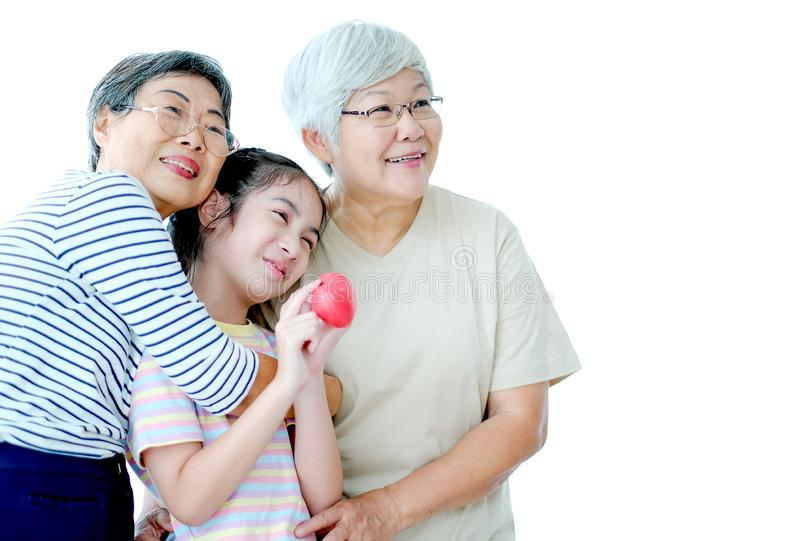 Two elderly women with young children hug together with smiling and all look to right side. Image is isolated on white background. With copy space stock photography