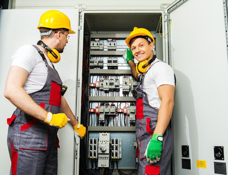 Two electricians on a factory royalty free stock image