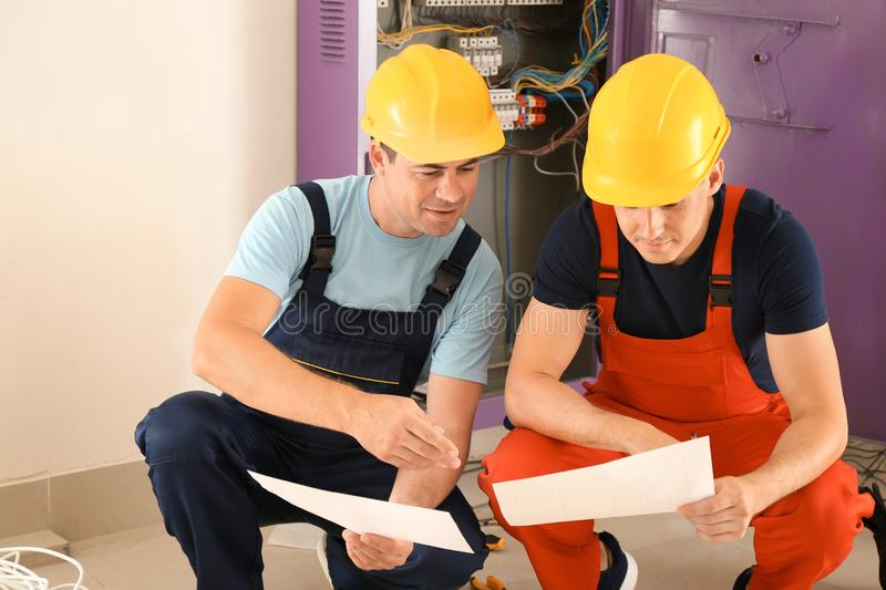 Two electricians with house plan near distribution board indoors stock images