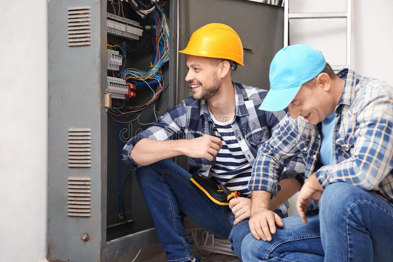 Two electricians near distribution board indoors stock photography