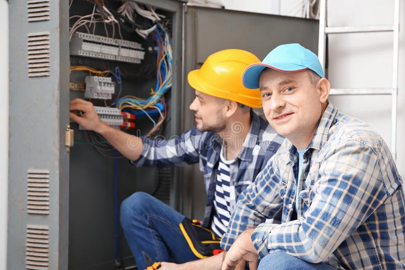 Two electricians near distribution board indoors stock images