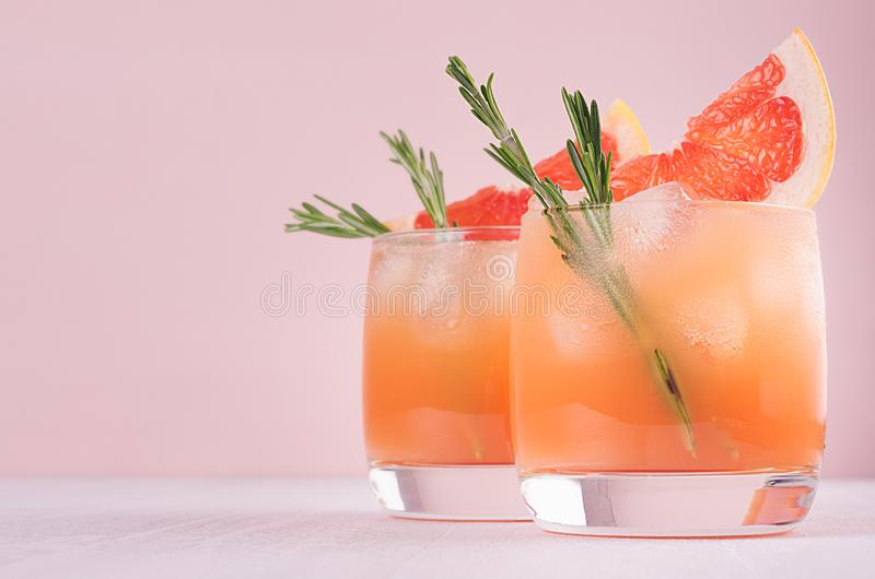 Two elegance cold wet drinking glasses with fresh grapefruit summer alcohol cocktail, ice, rosemary on fashion pink background. stock photo