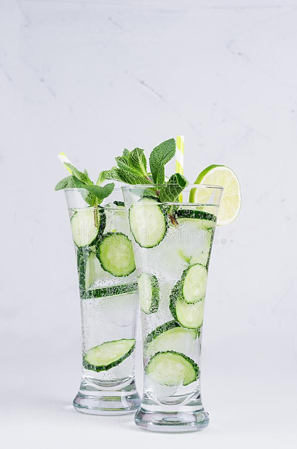 Two elegance glasses with cold detox water with slices cucumber, lime, mint, ice, straw on white wood plank, closeup. stock images