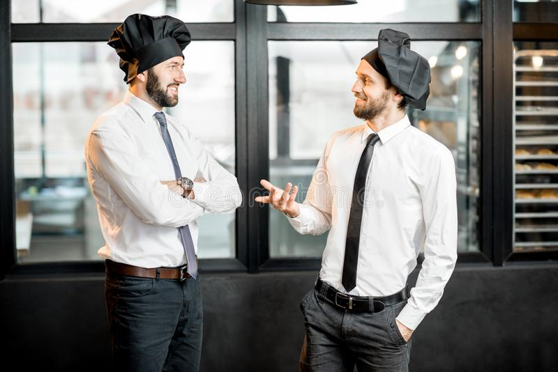 Bakers talking in the office. Two elegant bakers in white shirts and caps talking together in the office with bakery on the background royalty free stock photos