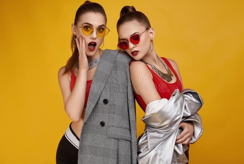 Two elegant glamor hipster twin girls in fashion red top, black shorts royalty free stock photos