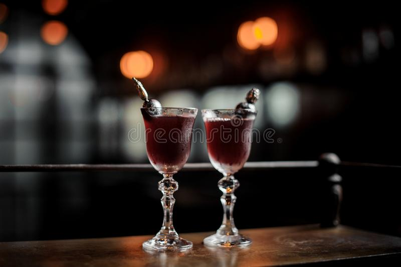 Two elegant glasses filled with fresh sweet and strong summer Arnaud cocktail on the dark blurred background of bar royalty free stock photos