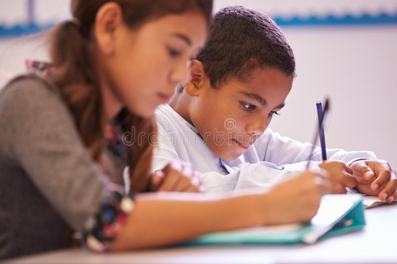 Two elementary school pupils working at desk during a lesson stock photos