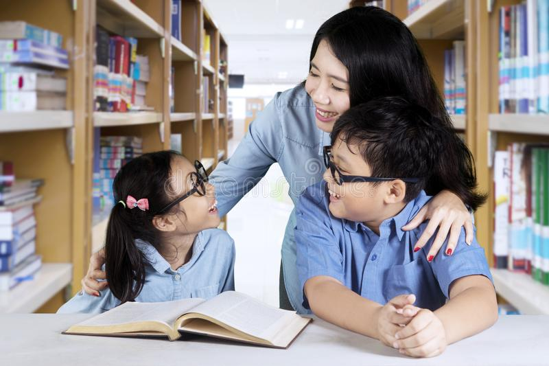 Two elementary students with teacher in the library stock images