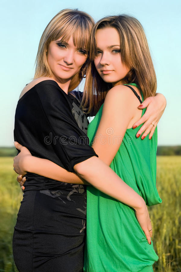 Two embracing smiling pretty girls royalty free stock photography