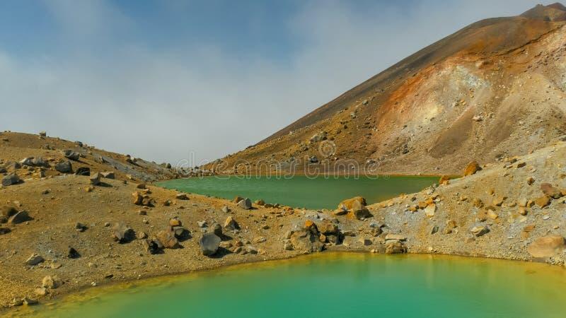 Two emerald lakes on the tongariro crossing. Low angle view of two emerald lakes on new zealand`s tongariro crossing royalty free stock images