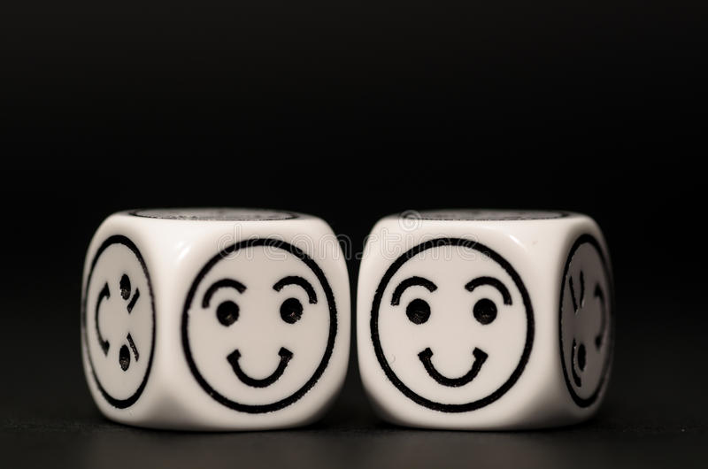 Two emoticon dice with happy expression sketch. On black background - stock photo royalty free stock photos