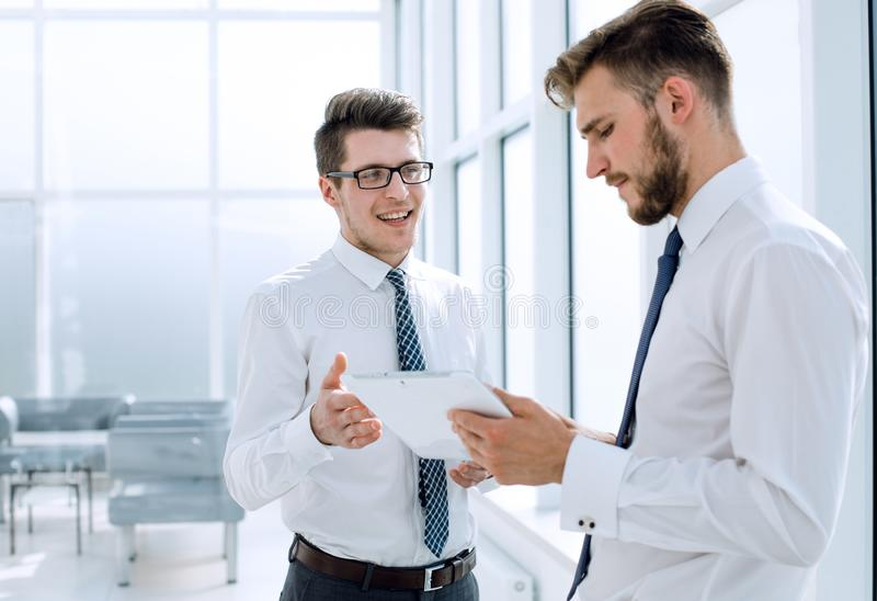 Two employees with a digital tablet discussing something standing in the office royalty free stock image