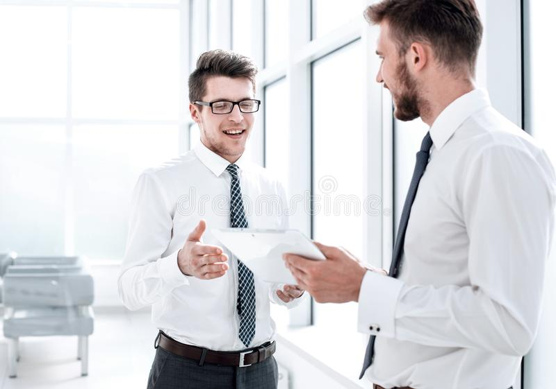 Two employees with a digital tablet discussing something standing in the office stock photography