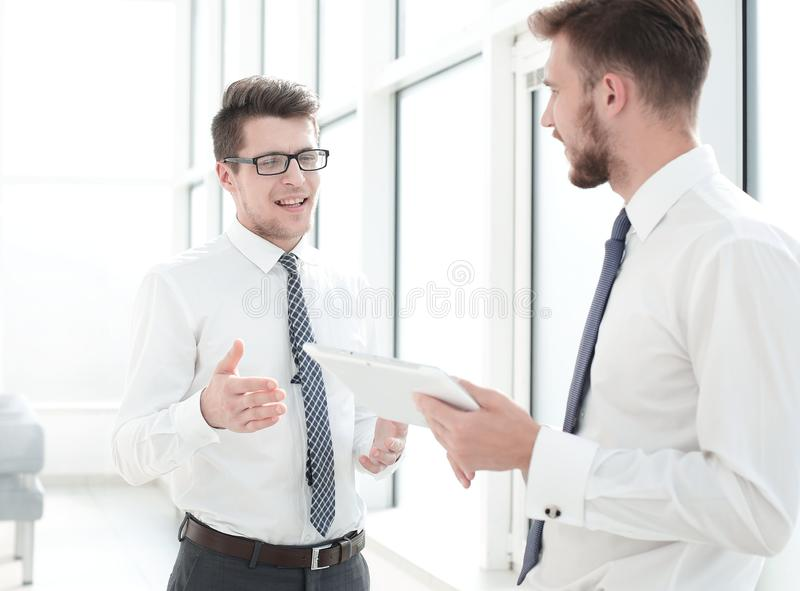 Two employees with a digital tablet discussing something standing in the office royalty free stock photography