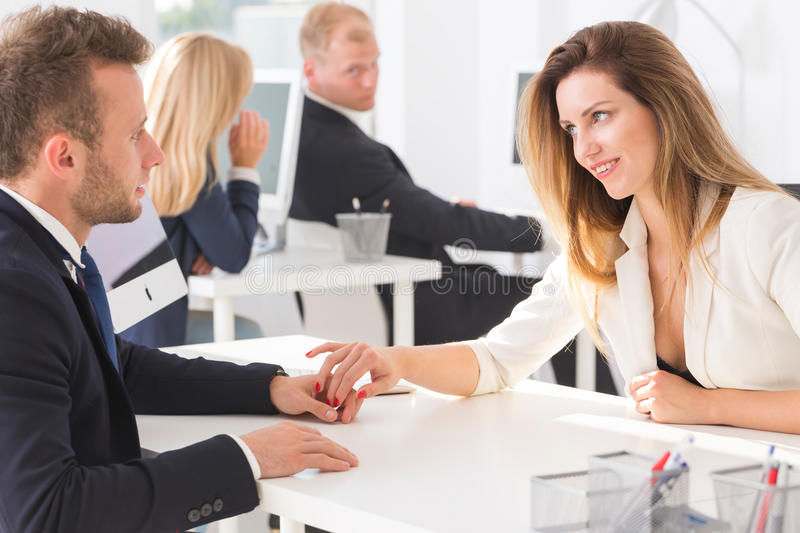 Two employees holding hands in the office stock images