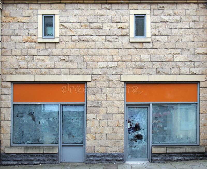 Empty abandoned shops on a street with whitewashed empty windows and blank store signs stock images