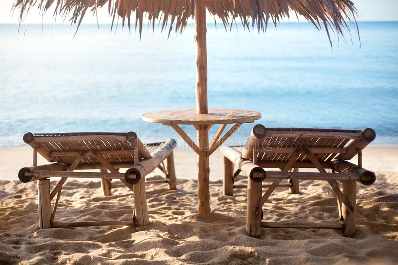 Two empty bamboo loungers and table under straw umbrella on white sand lonely beach, blue sea background. In the morning sun light, nobody, design for tourist royalty free stock photography