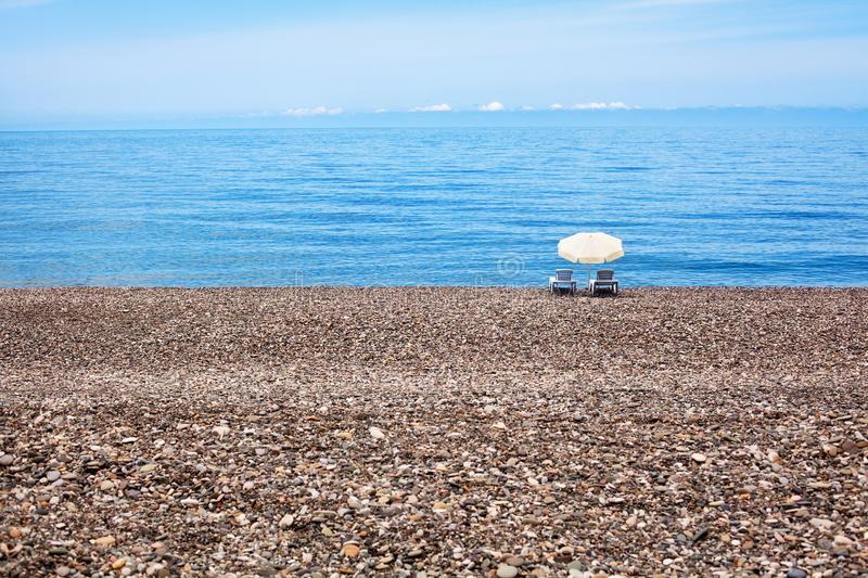 Two empty chaise lounges and white sun umbrella on beautiful lonely pebble beach, blue sea water, sky and horizon line background. Summer vacation banner stock photography