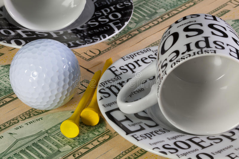 Two empty coffee cups and golf equipments stock images