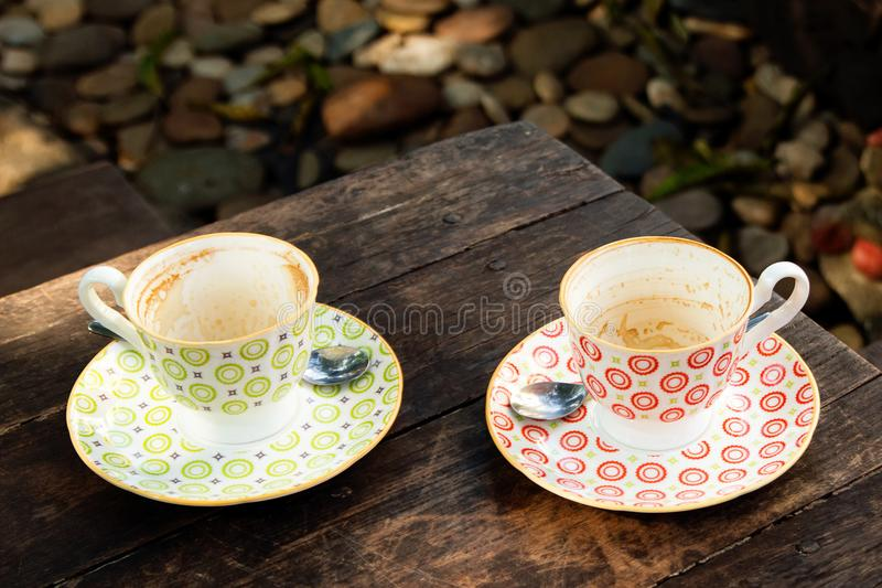 Two empty colorful cups after drinking coffee on a wooden table. stock photos