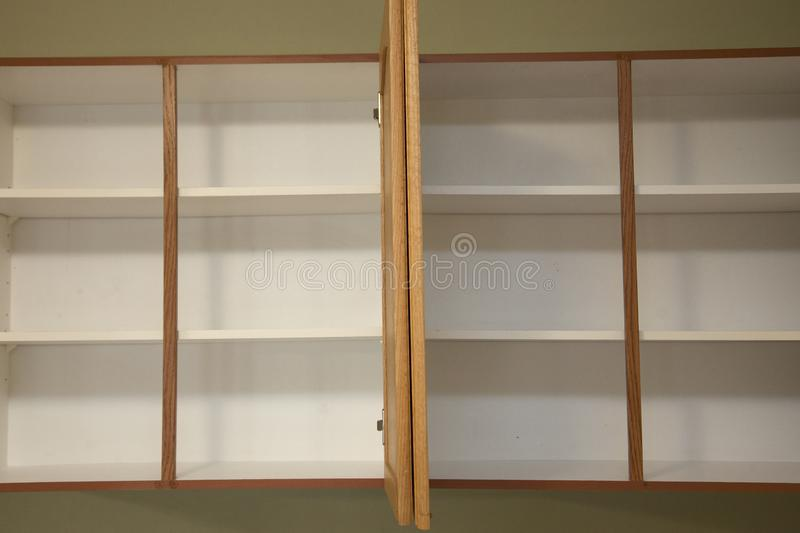Two empty cupboards in the kitchen. Empty bare kitchen shelves, in a vacant apartment or home with no food royalty free stock photos