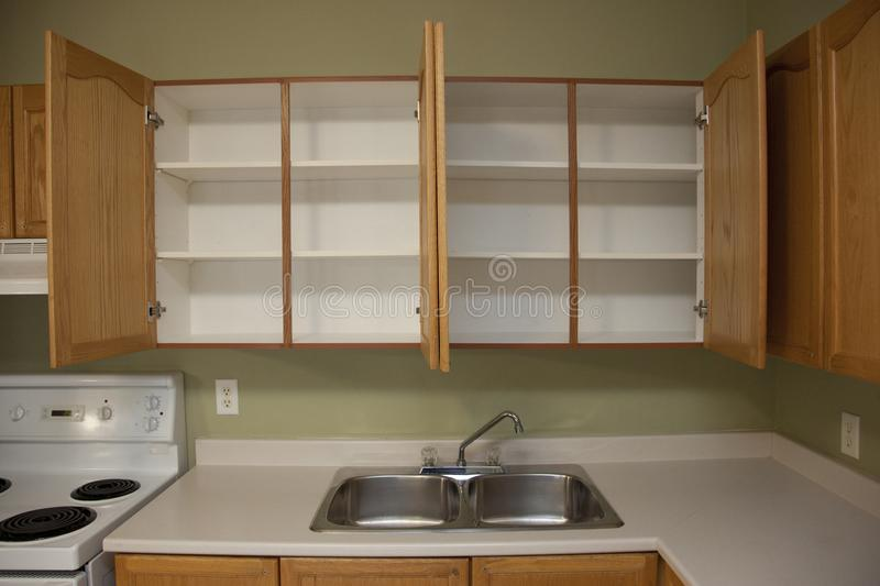 Two empty cupboards and a kitchen sink. Kitchen counter beside a kitchen sink with two empty cabinets above in a home or apartment stock photography