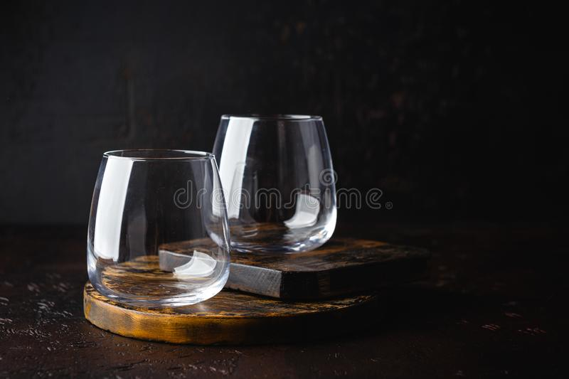 Two empty glasses on small wooden cutting board stock image