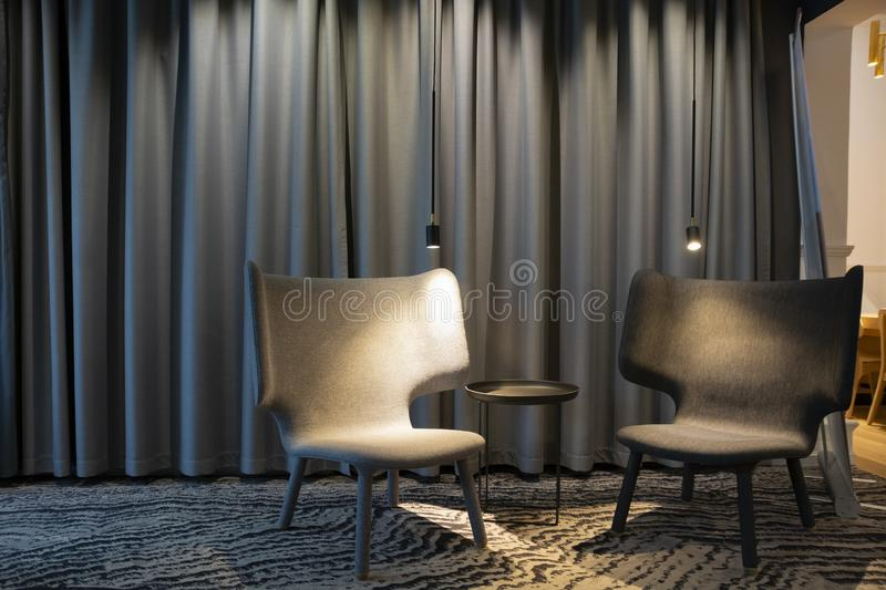 Two empty modern grey chair with lights and a table between. Curtains on a background royalty free stock image