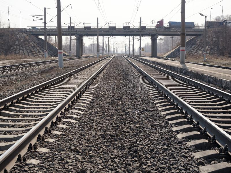 Two empty parallel railway lines, rails, sleepers, rubble close up, wide angle, toned brown, selective focus. Urban, industry, transportation freight and cargo stock photography