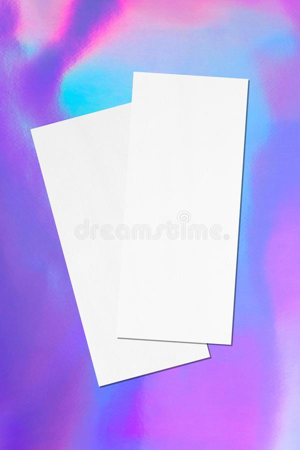 Two empty price-list or menu mockups lying diagonally on top of each other on holographic background. Two empty price-list or menu mockups lying diagonally on stock photos