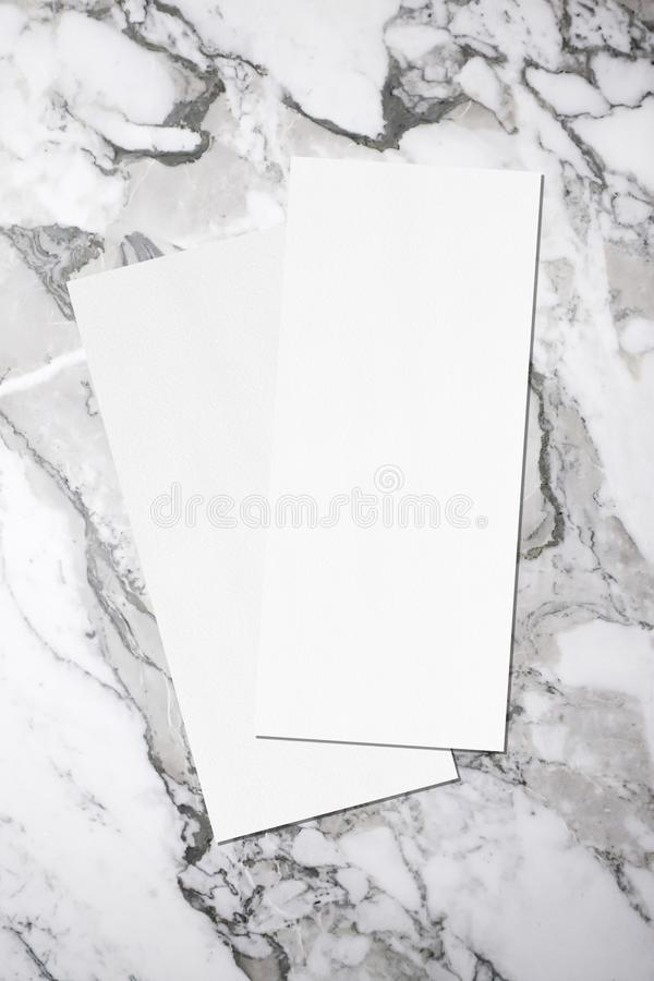 Two empty price-list or menu mockups lying on top of each other on grey marble background. Two empty price-list or menu mockups with soft shadows, lying stock photo