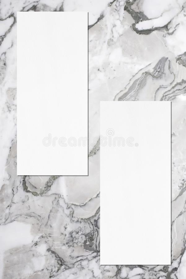 Two empty price-list or menu mockups lying on grey marble background. Two empty price-list or menu mockups with soft shadows lying on grey marble background royalty free stock image